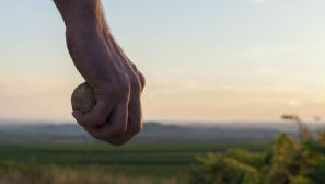 Hand holding a stone. Sky at the background. Sunset